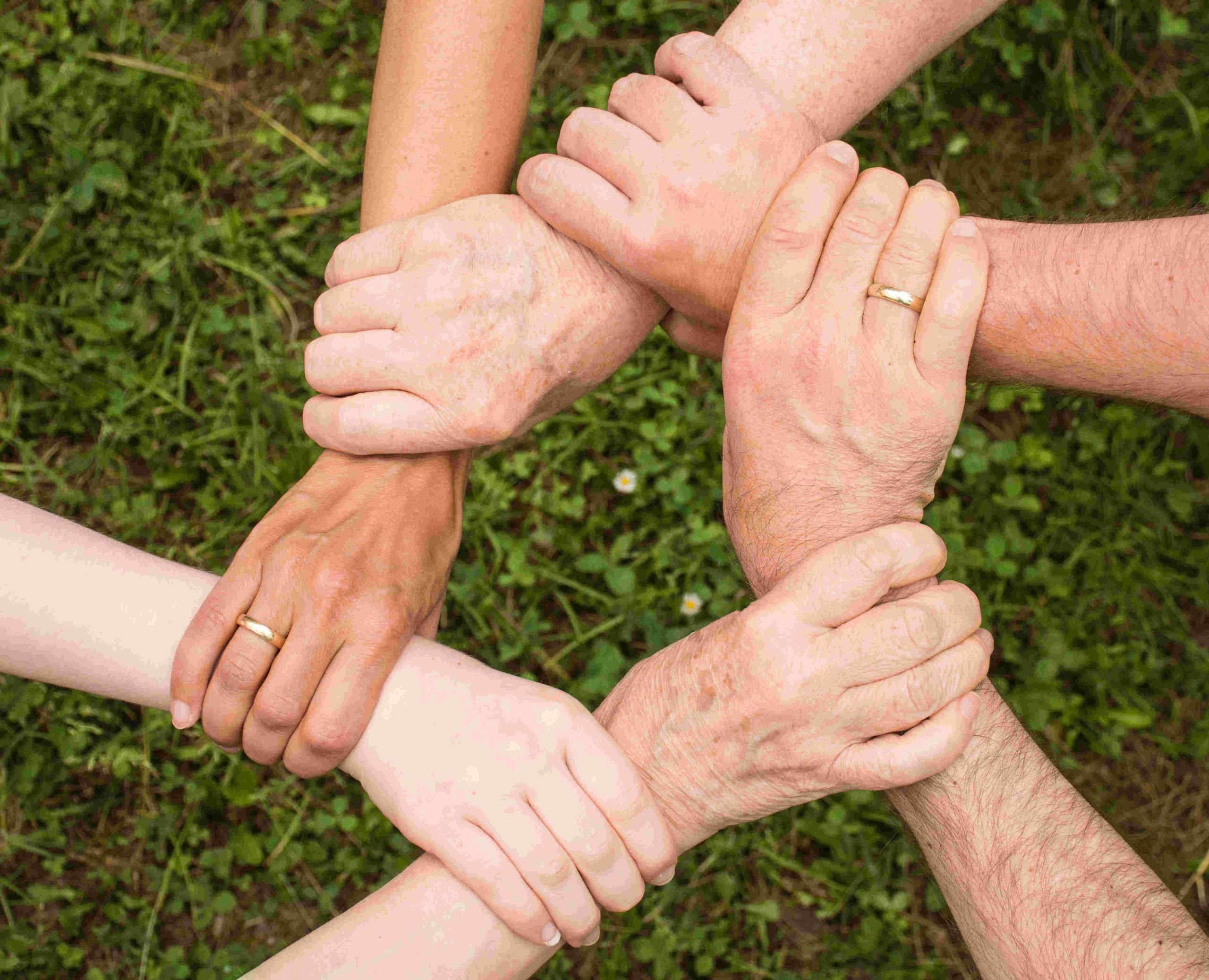 Sechs Hände bilden einen Kreis